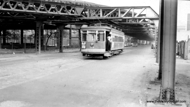 "CTA 114 heading east on 63rd street, just about to go under the Jackson Park branch of the ""L"". M. E. adds, ""At the right side of the picture in the foreground are two vertical posts that supported the structure that went south across 63rd St. to the lower 63rd St. yard. Therefore this picture was taken just about underneath that structure."" (Roy W. Bruce Photo)"