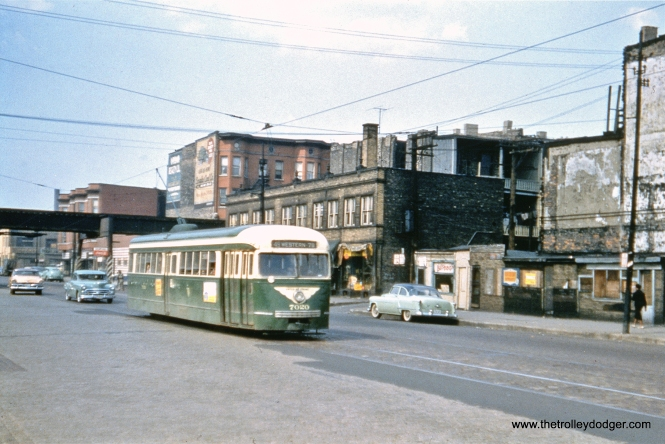"Prewar CTA PCC 7020, now converted to one-man operation, is southbound at Western and Maypole in May 1956, about a month before the end of streetcar service on route 49. The prewar cars were used for 364 days on this line. In the back, that is the Lake Street ""L"", which, oddly enough, does not have a stop on this busy street. (John F. Bromley Collection)"