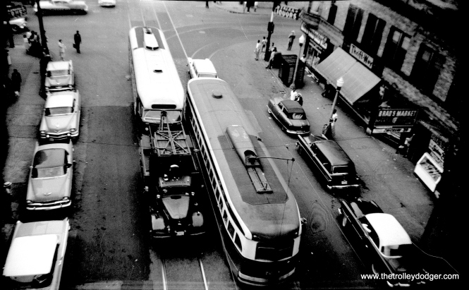 "This picture, most likely taken from an ""L"" platform, gives an excellent view contrasting the roof treatments on these two PCCs. 7203 is at right, in regular service, while the other car is being towed."