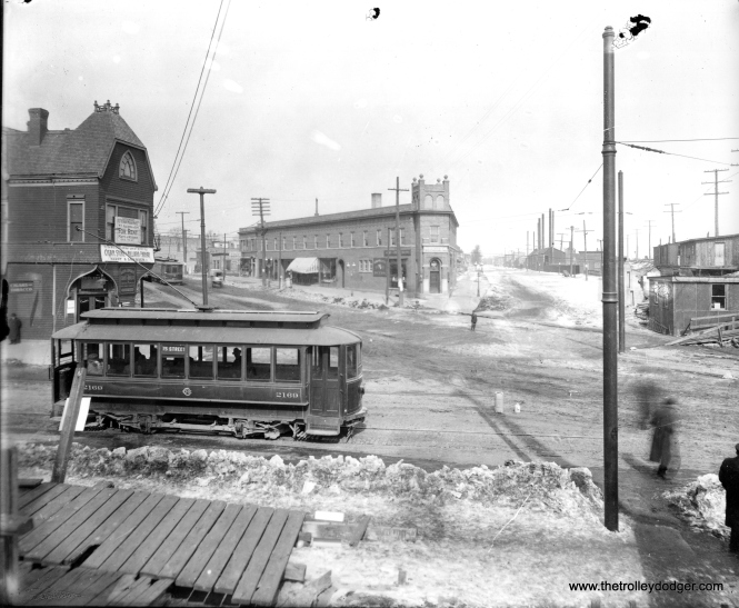 "Chicago City Railway car 2169 on the 75th Street route. According to Central Electric Railfans' Association bulletin 27 (July 1941), this car was part of an order of 69 closed cable trailer cars (with double door in bulkheads) built by Wells-French in 1896. These cars were electrified in 1908, and most were renumbered. My guess is we are at 75th and South Chicago. This picture would have been taken between 1908 and 1914, when CCR became part of the Chicago Surface Lines. If I am reading B-27 correctly, this car would originally have been numbered 2129. It was scrapped after CSL was formed. Bob Lalich adds, ""I agree, Chicago City Railway car 2169 is at 75th and South Chicago Ave. It appears that the Grand Crossing grade separation project was underway, judging by the construction shacks."""