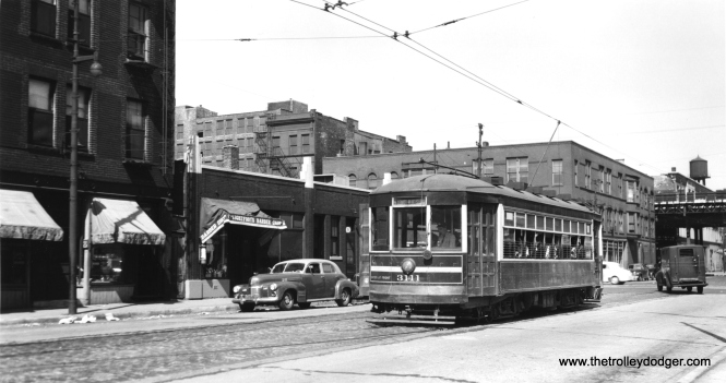 "CSL 3111 is westbound at 18th and State, just west of the South Side ""L"". I see a 1940s Cadillac at left. Andre Kristopans: ""Note also the nominal WB track has no overhead!"" (Joe L. Diaz Photo) M. E. adds, ""Andre Kristopans points out the westbound track has no trolley wire. That is because this photo shows the eastern terminal of the 18th St. line. The streetcar will switch over to the westbound track to continue west. Behind the streetcar is the 18th St. station on the South Side L. The streetcar's destination sign says Leavitt - Blue Island, which was the sign on a streetcar in an photo posted previously. You also have a photo at 18th and Sangamon. Together with your earlier photos, It seems the photographer was all over the 18th St. line that day."""