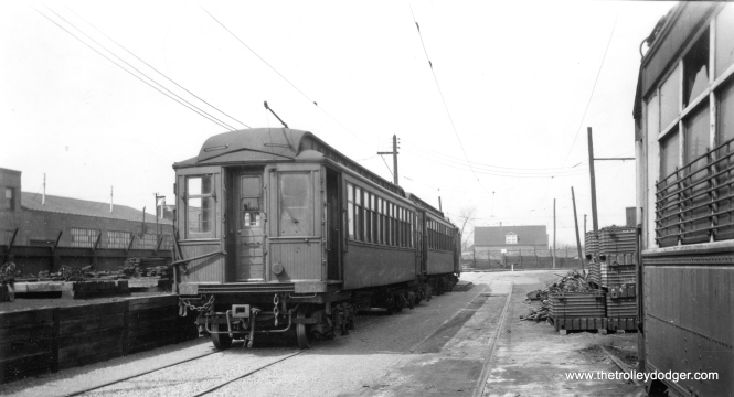 "CTA ""L"" car 3115 at West Shops in April 1949. This was one of the few places where CTA rapid transit cars and streetcars could operate on the same tracks, the other being at 63rd Street Lower Yard. The location is approximately 3900 W. Lake Street. There was a ramp, a rather steep grade in fact, connecting with the Lake Street ""L"", which lasted until 1987. Can that be a streetcar at right?"
