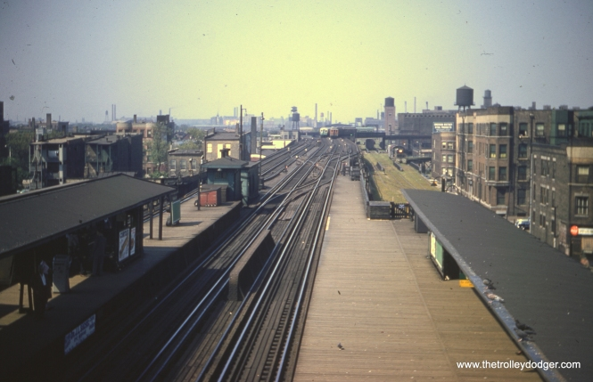 "The mount on this Kodachrome slide helps narrow down the time frame on this photo to 1955-57. We are at the Indiana Avenue station on the South Side ""L"", looking west. We posted a picture showing the view looking east at this station in a previous post. That picture shows a Kenwood shuttle train, but the wood cars in the distance here are very likely Stock Yards cars. Wooden ""L"" cars would not have been running on the Howard-Jackson Park-Englewood line, as that went through the State Street subway. According to Graham Garfield's excellent web site, Stock Yards shuttle cars would have stopped at the south platform (to the left in this picture) via a single track. Presumably, the two-car wood train in this picture is heading west, and the mainline train of 6000s is heading east. Running parallel to the ""L"" at this point, just to the north, is the Chicago Junction Railway, which built and owned the Kenwood branch of the ""L."" This part of the CJ was abandoned in the 1960s after the Union Stock Yards had dwindled down to next to nothing."