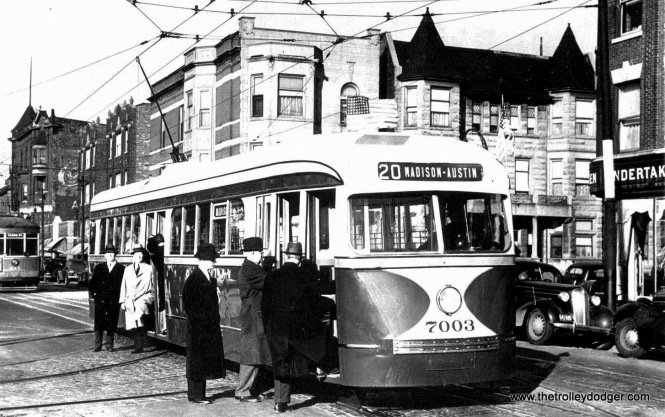 "Andre Kristopans comments on this 1930s photo: ""Look carefully at the shot of 7003 – it is a posed picture. Probably everybody is a CSL engineering department employee. Several things of note: 1) That is not trolley bus overhead. It is two positive wires side by side. Look at the street carefully. That is gauntlet track. Most carbarns had a gauntlet track so there would be fewer switches in the normal running rail. Besides, the TB wire on Pulaski existed as far as Maypole, then turned east into the shops in 1936. 2) Behind is a southbound Kedzie car. 3) Street is way too narrow to be anywhere on Madison. Conclusion – this is on Kedzie in front of Kedzie carhouse, and indeed 7003 is on the yard lead, loading up ""dignitaries"" for an inspection trip."""