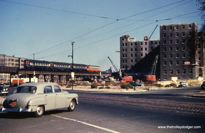 "The coming of summer also means more construction and demolition projects. A four-car CA&E train is seen on the old CTA Garfield Park ""L"" at Ogden on October 19, 1952. Demolition of buildings for the Congress Expressway is well underway."