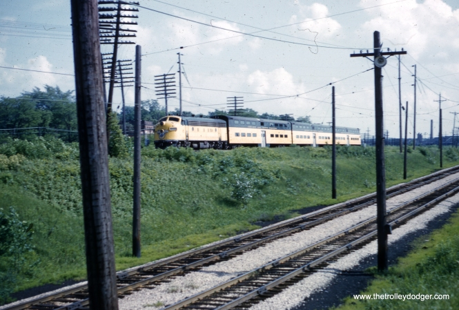 "This photo of a Chicago & North Western train of bi-levels was taken by Al Clum in June 1962. But where? One reader writes, ""The descending tracks in the foreground of the photo are leading to the North Shore Line's North Chicago Junction Station. The CNW train is on the CNW embankment between Great Lakes to the south and North Chicago to the north. Since the headlights are not turned on on the locomotive, one would presume that the train is a push-pull heading south."""