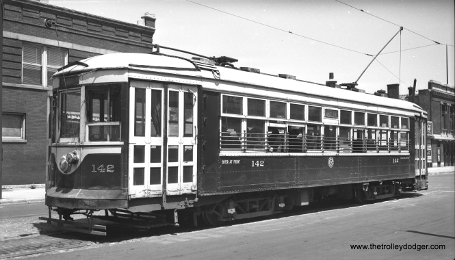 "Chicago & West Towns 142 at the east end of the Lake Street line at Austin Boulevard on July 4, 1946. The building at right is the old Park Theatre. This is a ""sister"" car to the 141, now preserved in operating condition at the Illinois Railway Museum."