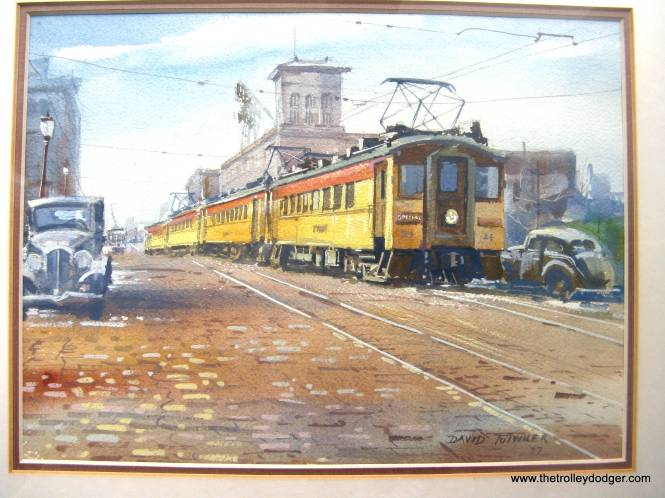 "George Foelschow: ""The latest Trolley Dodger installment, which included a photo of a South Shore Line train on East LaSalle Avenue in South Bend, reminded me of a watercolor painting I acquired before moving from Chicago in 1978. The artist is David Tutwiler and the painting is dated (19)77. It depicts a similar scene. I thought you may want to share it with Trolley Dodger readers."" Thanks, George!"