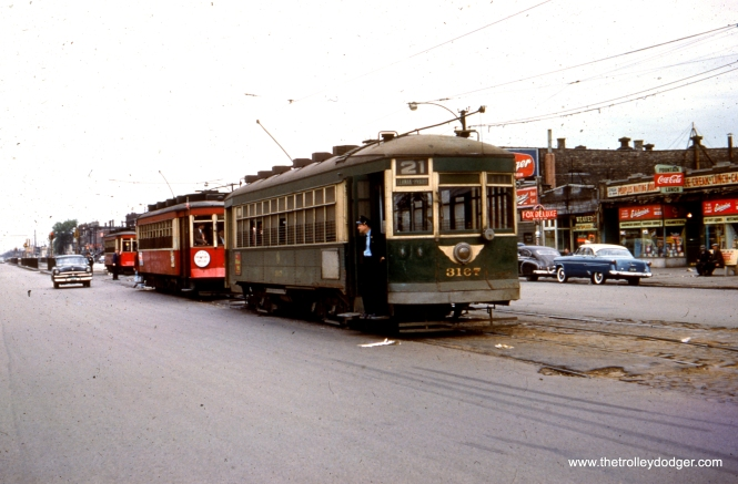 "CTA regular service car 3167, painted green, is at Cermak and Kenton, west end of route 21. Red cars 479 and 473, at the rear, are on the famous CERA ""farewell to red cars fantrip."" The date is May 16, 1954, two weeks before the end of red car service in Chicago."