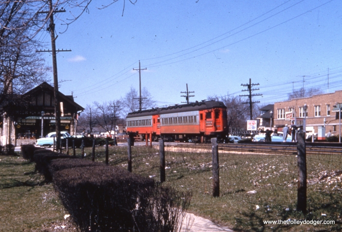 "This undated 1950s photo shows a westbound Chicago, Aurora & Elgin train (cars 406 and 41x) at the Villa Park station. According to the Great Third Rail web site, ""The station was rebuilt again in 1929. During this reconstruction, the eastbound platform was moved to the west side of Villa Avenue with the construction of an expansive Tudor Revival station designed by Samuel Insull's staff architect, Arthur U. Gerber. The westbound platform remained in place and was outfitted with a flat roofed wooden passenger shelter. Villa Park was one of a few stations to survive the demise of the Chicago, Aurora and Elgin. Both it and Ardmore (the next station west) were purchased by the village of Villa Park and refurbished with an official dedication by the Villa Park Bicentennial Commission on July 5, 1976. It is now home to the Villa Park Historical Society which hosts an annual ice cream social on July 3, the anniversary of the day the CA&E ended passenger service."""