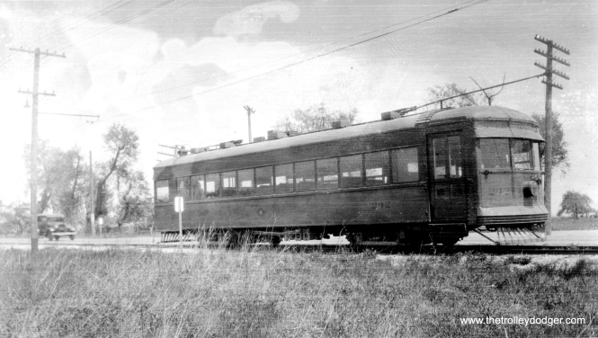 "This is car number 242 of a 1920s side of the road interurban, but which one? Could it possibly be the Chicago and Joliet Electric Railway, which connected the Chicago Surface Lines and the Chicago, Ottawa & Peoria? They did have a car 242, but I'm not sure this is the same car. Don's Rail Photos says, ""242 was built by Cummings Car & Coach Co. in 1927."" They have another picture of C&JE car 242 here for comparison. If this is that car, it would narrow down the time when this picture could have been taken to between 1927 and 1933. (We previously ran a picture of car 242 in a previous post.)"