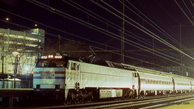 This photo shows Amtrak E-60 # 602 with Train # 40 the THREE RIVERS stopped at Trenton. It is illuminated by the headlight of a NJT train.