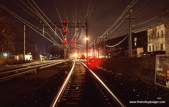 The view from the platform shows signal lights and the Catenary wires.