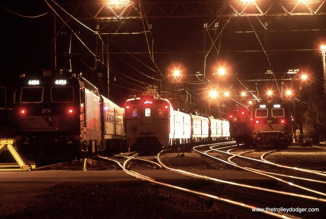 The headlight of an approaching train illuminates the sides of a Arrow MU set in the Gladstone yard 12/11/98