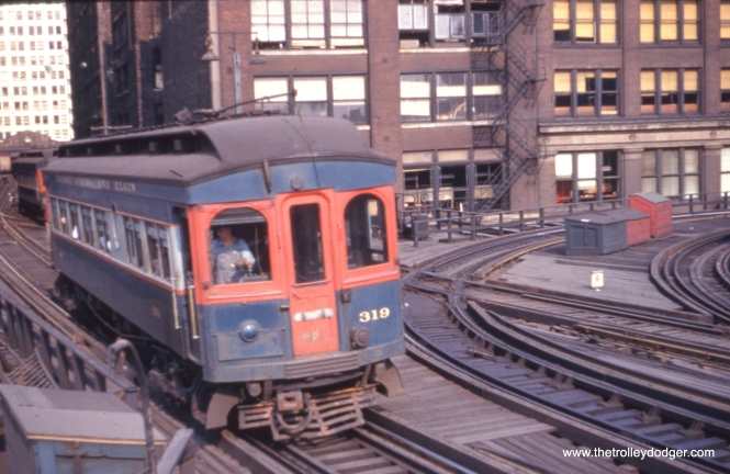 "Chicago, Aurora & Elgin wood car 319 heads west, having just left the CTA's Wells Street Terminal, sometime prior to the end of CA&E service downtown in September 1953. This was a stub-end terminal, and the tracks at right curved around to Van Buren and connected to the southwest corner of the Loop ""L"". In 1955, that connecting track was removed as part of the construction of lower Wacker Drive. A new connection to the Loop was made by extending two tracks through the old Wells Street Terminal, which was by then no longer in use. The CTA's Garfield Park trains continued to use this connection until June 1958, when the Congress median line opened. Parts of the old ""L"" structure here were not demolished until the early 1960s."