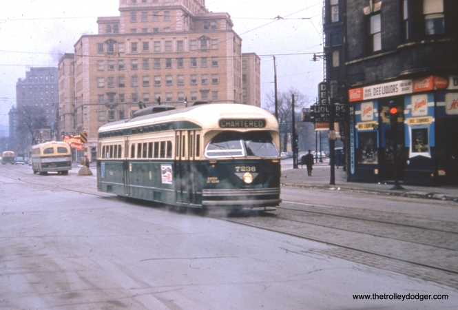 "CTA postwar PCC 7236 is shown northbound at Clark and Armitage on Sunday, December 18, 1955 in fantrip service. It was preferable in this period to run fantrips on weekends, since regular service on these lines was now being operated by buses, such as the ones shown in the background. We have run three other photos from this same fantrip in previous posts. Red car 225 was used ahead of this car. Since the trip organizers had advertised that car 144 would be used, they put a piece of oilcloth with that number on it over the Pullman's actual number. I also wrote about this same trip in the post The Old Math (144 = 225) March 13, 2013 on the CERA Members Blog. At that time, I thought the date of the trip was 1956, but a variety of sources since then say it was actually 1955. George Foelschow adds, ""The tan building directly behind the car is the North Park Hotel, the apex of the Old Town Triangle, site of the Chandelier Room, where I cast my first vote in 1960, since I lived just south of there on Lincoln Avenue. Sadly, the streetcars and trolley wires were gone by then, and only the tracks remained for a time."""