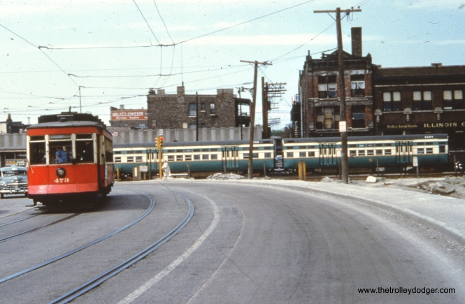 "This photo was marked as being taken in April 1951. Unfortunately, what the picture shows makes that date impossible. The buildings behind the ground level ""L"" show that this is Western Avenue at Van Buren, during the 1953-58 rerouting of part of the Garfield Park ""L"". Red car 473 is on a curve because the tracks are on a shoo-fly while the bridge that would go over the Congress (now Eisenhower) expressway was under construction to the left of this view, which looks north. This phase of construction, and the presence of car 473, would imply that this picture actually dates to May 16, 1954, when this car and 479 were used on a CERA ""farewell to red cars"" fantrip on Chicago's streetcar system. Meanwhile, a two-car train of flat door 6000-series ""L"" cars (6049-6050), with numbers painted on their roofs, proceeds on the ponderously slow 2.5 mile temporary trackage."
