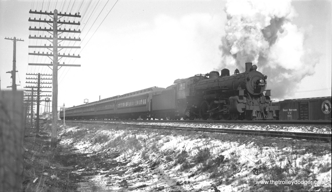 "In the twilight days of steam, C&NW locomotive 532, a 4-6-2, heads a commuter train in February 1956. Although this negative is marked as having been taken at Euclid Avenue in Oak Park, where UP freight and Metra commuter trains now share space with the CTA's Green Line rapid transit, this certainly looks like it was taken somewhere else at ground level. (Bob Selle Photo) Andre Kristopans: ""The CNW ""Euclid Ave"" shot most likely is about where Kilpatrick Av now crosses the tracks. If one blows up the photo, you see a railroad overpass in the background that certainly looks like the BRC bridge at Kenton. Box cars on right would be on one of the tracks at 40th St Yard, while the lower-level track in foreground would be an industrial lead. Train would be EB."""