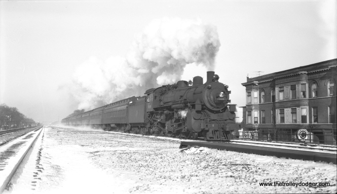 "Chicago & North Western loco 608, a 4-6-2, heads an eastbound commuter train at Oak Park Avenue on March 23, 1955. This shows how the wide C&NW embankment made it possible, within a few years, to elevate the outer end of CTA's Lake Street ""L"". In the process, several close-in C&NW stations were closed. (Bob Selle Photo)"