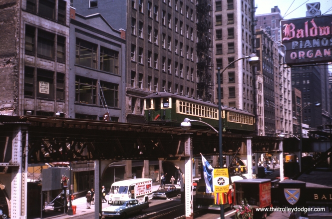 "This July 1963 view shows the Wabash leg of Chicago's Loop ""L"" between Van Buren and Jackson. We are looking north, so the buildings behind the train of CTA 4000s are on the west side of the street. As you can see by the sign advertising Baldwin pianos and organs, this was once Chicago's ""Music Row."" The flagship Rose Records location was near here, as were Carl Fischer, the Guitar Gallery, American Music World and many others. The Chicago Symphony is still nearby, but nearly all the other music-related retailers are now gone from this area. You can just catch a glimpse of the iconic Kodak sign that still graces Central Camera under the ""L"". The old North Shore Line station, which closed about six months before this picture was taken, would have been up the street on the right just out of view. Until 1969 trains operated counterclockwise around the Loop on both tracks, so we are looking at the back end of this Lake Street ""B"" train. Adams and Wabash station is at the far right of the picture."