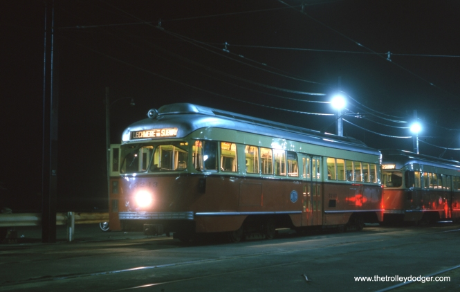 "It's August 1963 in Boston, and MTA PCC 3243 stands ready for another trip on the Green Line. Phil Bergen writes, ""The night view of the Boston PCC that appears in today's posting was taken at Riverside terminal. Although picture window PCCs were originally used on this line, other PCCs were added to meet the demand. The side roll sign, once enlarged, indicates this is a Riverside car, and the terminal itself is the only place where there were multiple tracks."" The Riverside line started running on July 4, 1959 and occupies a right-of-way once used by a steam commuter railroad. It is considered a pioneer in what we today call ""light rail."""