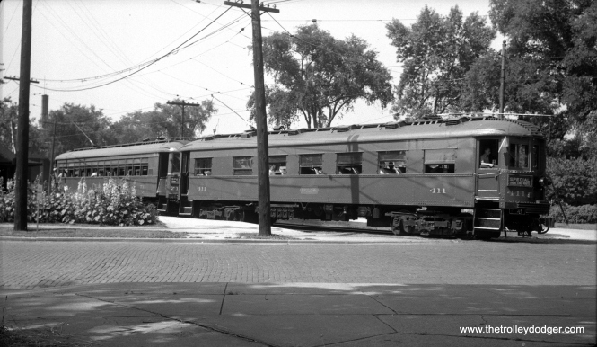 "North Shore Line cars 411 and 715 at an unidentified location. Don's Rail Photos says, ""411 was built as a trailer observation car by Cincinnati Car in June 1923 #2640. It was out of service in 1932. 411 got the same treatment on February 25, 1943, and sold to Trolley Museum of New York in 1963. It was sold to Wisconsin Electric Railway & Historical Society in 1973 and sold to Escanaba & Lake Superior in 1989."" As for the other car, Don says, ""715 was built by Cincinnati Car Co in 1926, #2890. It is modernized in 1939 and purchased by Mid-Continent Railroad Museum in 1963. It was sold to Wisconsin Electric Railway Museum in 1967 and then sold to Fox River Trolley in 1988."""