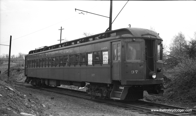 "Laurel Line (Lackawanna and Wyoming Valley Railroad) car 37 at the G.E. plant on the Minooka branch on May 9, 1948. The occasion was an ERA (Electric Railroader's Association) fantrip. Nearly all this Scranton, Pennsylvania interurban was third-rail operated on private right-of-way, something it had in common with the Chicago, Aurora & Elgin. Some have wondered if the Laurel Line's fleet of steel cars, which ended service at the end of 1952, could have been used on the CA&E. They appear to have been too long to operate on the Chicago ""L"" system, but I do not know if such clearance issues would have kept them from running west of Forest Park. As it was, all these cars were scrapped, and ironically, some thought was given later to restoring a CA&E curved-side car as an ersatz Laurel Line replica. Wisely, it was decided against this."