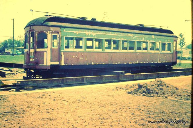 "A color version of the same badly faded Anscochrome image. Frank Hicks adds, ""Neat photo! The car is definitely still in CA&E red and light blue/gray. The color is badly washed out but that's definitely the same lettering that the car left Wheaton with (Brookins lettered the car for Columbia Park & Southwestern as soon as they repainted it green). It looks like the car has been rigged for road transport. I'm guessing that this photo was taken when the 36 arrived at the Columbia Park trailer park for the first time. If memory serves, the CA&E cars that went to Brookins traveled to Ohio on their own wheels and sat on a siding near Columbia Park for a period before being trucked over to Trolleyville. I'd guess that the splotchy appearance is due to white primer or paint being applied over bad spots in the original paint during its period on the siding."""