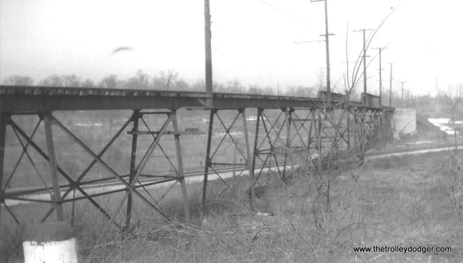 "Tony Manthos: ""As for the trestle, it's a long shot, just in case you have encountered it before or know the site. The main line underneath is very well maintained. They obviously didn't want an interurban diamond getting in their way."" Don Ross: ""The trestle was Milwaukee at Grafton."" http://donsdepot.donrossgroup.net/dr2672.htm On the other hand, Scott Greig says, ""The Milwaukee Electric viaduct identified as Grafton is actually the viaduct near Mequon quarry. The view is looking north, from the side of Highway 57."""