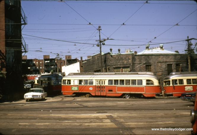 "MBTA (Boston) PCC 3147 at an unidentified location in October 1966. Could this be the old Braves Field loop? Tunnelstation writes:""The Boston PCC picture is located at the end of the ""C"" line near the Chestnut Hill Reservoir off Beacon Street. The scene is the exit from the Reservoir Car yard out to the street which also serves as the end of the line return loop going to Downtown Boston. That is one of the oldest continuous running trolley lines in America and is still in service today using cars built in Japan."" Beacon Street is the MBTA Green Line ""C"" branch."