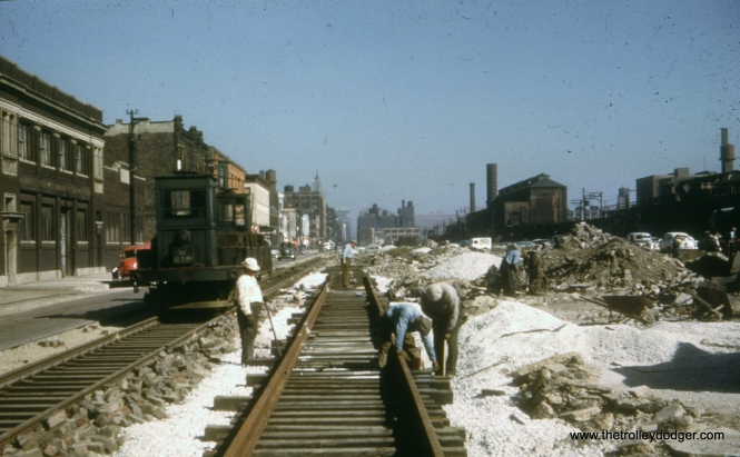 "In this undated photo, probably taken circa 1952, tracks are being laid in the southern half of Van Buren Street to create a temporary right-of-way for the Garfield Park ""L"", to allow the demolition of 2 1/2 miles of the old structure that were in the way of Congress (now Eisenhower) expressway construction. At right, you can see the old Throop Street Shops. This temporary alignment was used from September 1953 to June 1958."