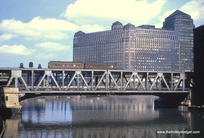 "A two car train of Lake Street ""L"" cars crosses the Chicago River with the Merchandise Mart in the background, probably in the early 1950s."