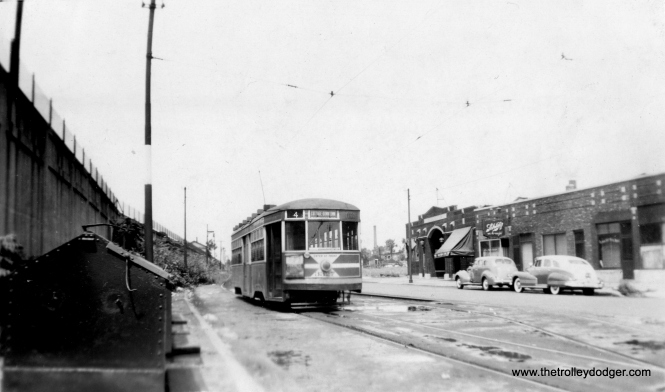 CSL/CTA Sedan 3327 is shown in the late 1940s at Cottage Grove and 115th, south end of route 4. The Illinois Central Electric suburban service is at left on an embankment.
