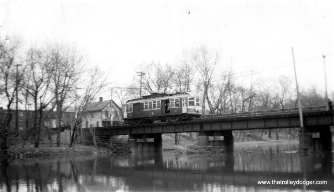 "Chicago & West Towns Railways line car #15. I believe this is crossing the DesPlaines River, possibly on a 1948 fantrip just prior to abandonment, and the buildings shown are on the east bank. Don Ross: ""15 was built by Pullman Car in 1897 as Suburban RR 512. It was renumbered 515 and rebuilt as 15 in 1927. It was rebuilt in 1940 and scrapped in 1948."" (Charles Able Photo)"