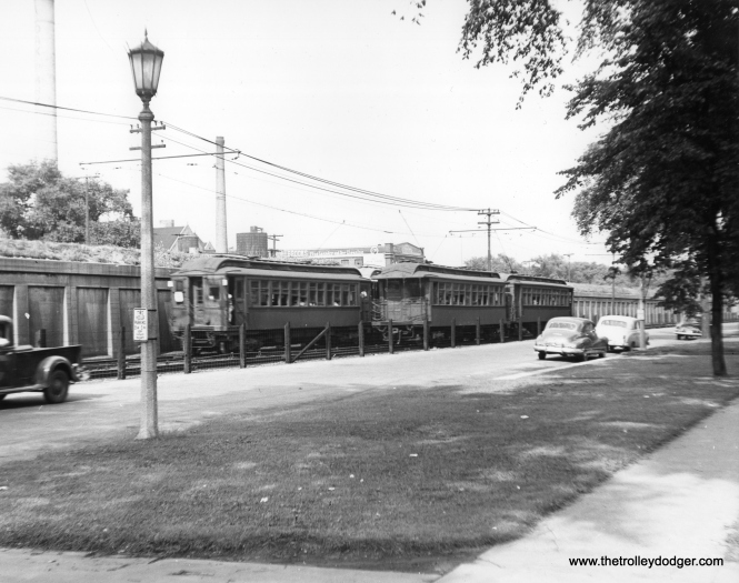 "Wooden ""L"" cars are still in use on the Lake Street ""L"" in this July 1951 view. The outer 2.5 miles of line ran on the ground, alongside auto traffic next to the Chicago & North Western embankment, where the tracks were relocated in 1962. The last woods ran on this line circa 1955. The distinctive old fashioned street lights and the Brooks Laundry and Dry Cleaning company peg this as Oak Park, but not all the right-of-way through the village was fenced off as we see here. Overhead wire was used. (Subsequent research shows that the Brooks Laundry was located at the corner of North Boulevard and East Avenue, so we are a block or two west of there along South Boulevard.)"