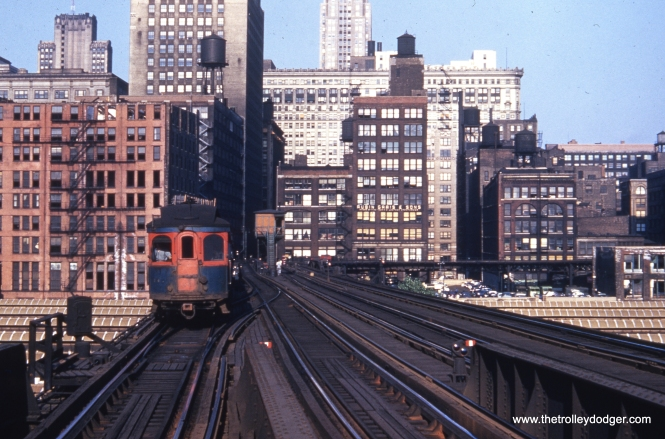 "A wood CA&E car in the 140-series heads west of the Loop on the four-track section of the Met ""L"" in the early 1950s. Below the ""L"", you see the Union Station train sheds where the Burlington Northern commuter trains run."
