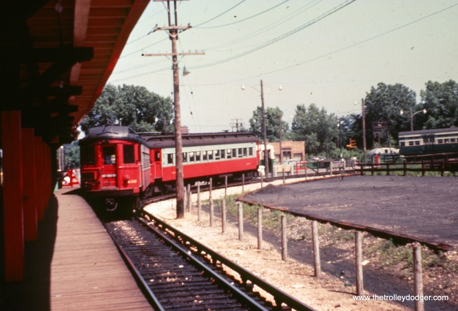 CA&E 430 heads up a two car train at DesPlaines Avenue in the 1950s, while some CTA 6000s are at right.