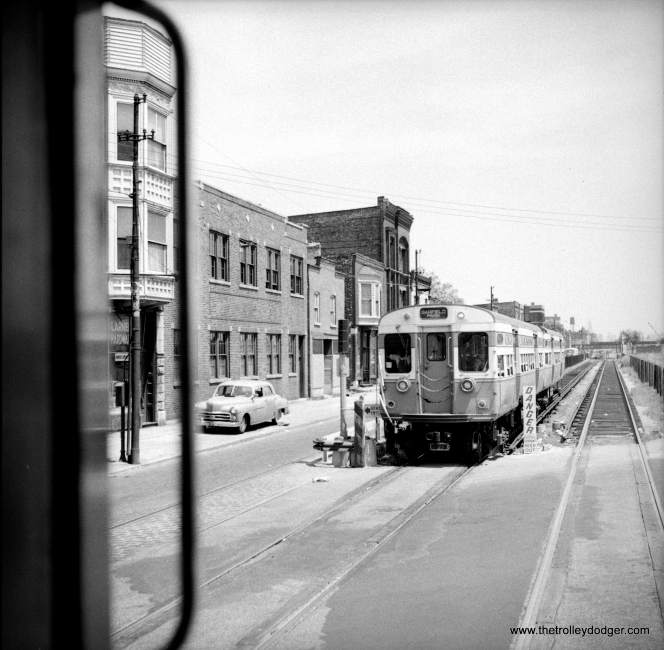 "The Van Buren Street temporary trackage as it appeared on July 17, 1954. The two-car train of flat-door 6000s may be 6071-6072. As for the cross street, my guess is California Avenue (2800 W.) meaning we are near the west end of the 2 1/2 miles of temporary right-of-way. There is a CTA bus just barely visible behind the train. Since the ""L"" made no stops along this section, bus service continued on Van Buren, even though it was only half a street for five years. Just to the left of the train, you can see streetcar trackage that would have been used until 1951. (Ed Malloy Photo)"