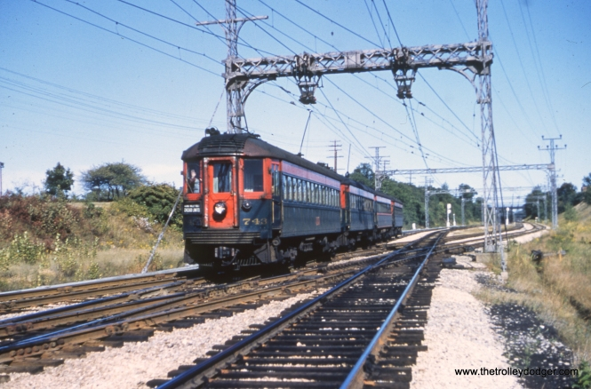 """NSL 743 and train at Green Bay Junction. Jerry Wiatrowski: """"NSL 743 and train are on the Skokie Valley route westbound crossing the Mundelein branch at Lake Bluff. The Green Bay Road overpass can be seen in the background."""" Joey Morrow: """"NSL 743 is at Green Bay junction, the catenary poles are still there today. It parallels IL-176 (Rockland Ave)."""""""