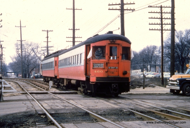"CA&E 460 and an older car are in fantrip service during the late 1950s. Nancy Grove Mollenkamp writes: ""This is at West Street looking west in Wheaton. The bridge over Liberty Drive at the start of the Elgin branch is seen in the background."""