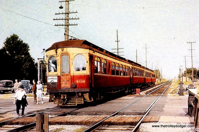"""Chicago, Aurora & Elgin 309 heads up a four-car train of woods circa 1940. This """"coffee and cream"""" paint job is not often seen in color pictures. This one, however, has the appearance of being hand-colored, most likely not digital, either. The original was faded, which would not happen with digital. This is more like an old colorized postcard."""