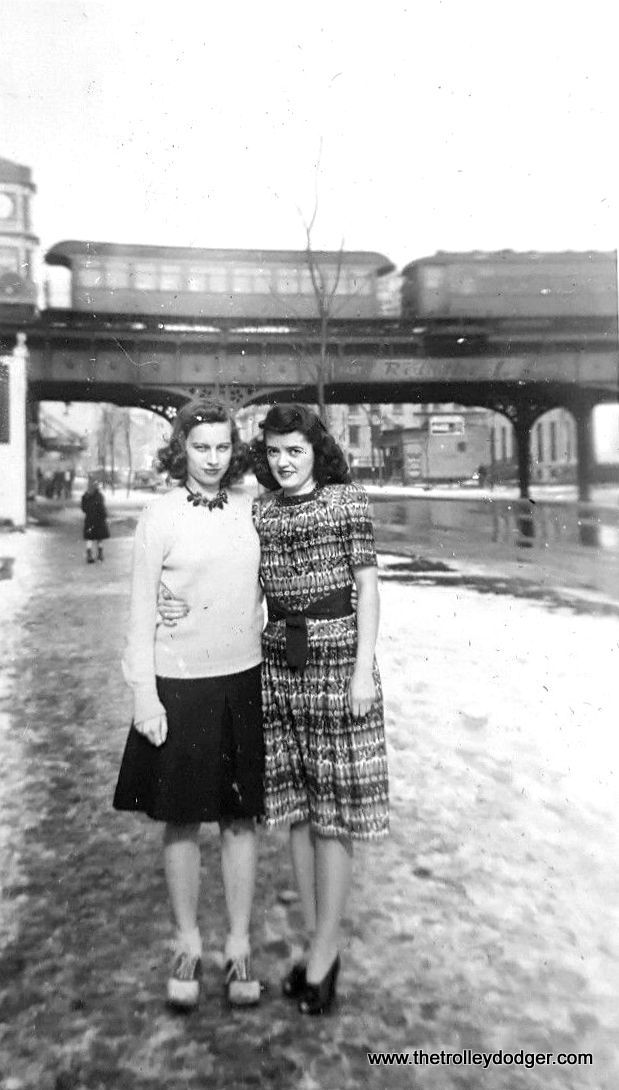"""This Chicago """"mystery photo"""" showing two young women is dated 1943. But where was it taken? The """"L"""" structure in the background has some ornamentation, and we see a gate car as well as a 4000. Since the 4000s were all put onto the State Street subway when it opened in October 1943, this picture probably dates to a late snowfall in spring."""