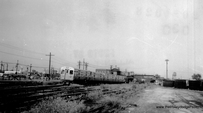 "At first, I had difficulty determining this location, but soon figured out that the station at rear is Laramie on the old Garfield Park ""L"". I believe we are looking east from Lockwood, where there was a grade crossing. The bulk of the yard was to the east of Laramie, although there were storage tracks for some cars west of Laramie, such as a small area that was once used for mid-day storage of CA&E trains. On the left of the picture, we see CTA buses along Harrison, and the gas station was located at the intersection of Harrison and Laramie. The Eisenhower Expressway is now to the right of this picture. The growth along some of these tracks would seem to indicate they were not being used much for storage by the time this picture was taken in the 1950s. (Allen T. Zagel Photo, George Trapp Collection)"