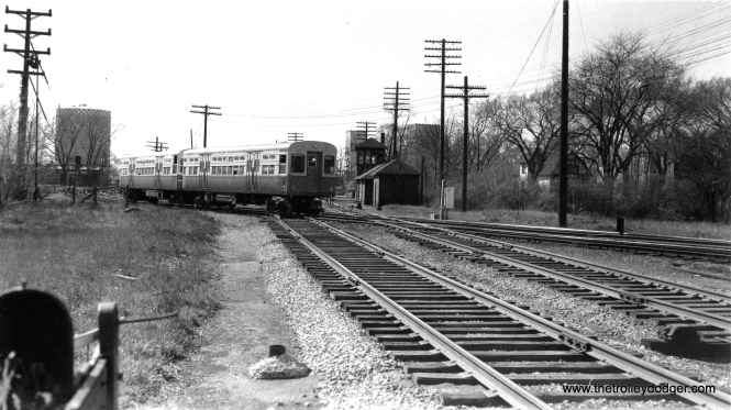 "The CTA's Garfield Park ""L"" trains crossed the B&OCT freight tracks at grade between Harlem Avenue and DesPlaines in Forest Park. We are looking west, and the large ""gas holder"" tank at left was a local landmark for many years. Now, these tracks are grade separated along the Eisenhower Expressway right-of-way. (Allen T. Zagel Photo, George Trapp Collection)"