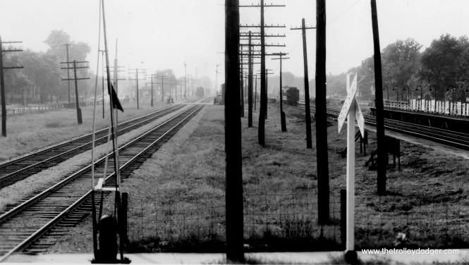 "I believe this photo shows the view looking west from Oak Park Avenue along the old Garfield Park ""L"". The B&OCT tracks were to the south of the ""L"", and we can even see a steam locomotive on a siding in the distance, serving businesses to the south. The eastbound and westbound ""L"" platforms here were on different sides of Oak Park Avenue. In the distance, we can see the next station west at Home Avenue. This is now the location of the Eisenhower Expressway, and all these tracks are now on the south side of the highway at this location, in an open cut. The only freight siding still in use along here is the Ferrara Pan Candy Company in Forest Park, about a mile west of here. (George Trapp Collection)"