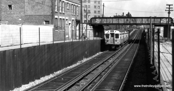 "The Van Buren trackage at Rockwell, showing the underpass trains used to clear the C&NW/PRR trackage. Notice how here, the CTA tracks are in the middle of Van Buren, instead of simply taking up the south half. This permitted a narrow lane on each side of the ""L"". To the south, this allowed construction workers access to both sides of the railroad embankment. We are looking east. (George Trapp Collection)"