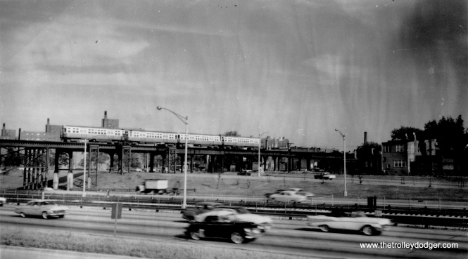 "In this late 1950s photo, we see the Garfield Park ""L"" crossing the Congress Expressway at Sacramento. We are looking to the south. The ""L"" continued to use the old alignment in those places where it was not directly in the expressway footprint. Between Sacramento (3000 W.) and Kostner (4400 W.), the ""L"" actually ran to the south of the expressway. At Kostner, the ""L"" again crossed the highway, this time at an angle, taking it to the north. North of this picture location would have been the Sacramento curve and a ramp connection to the Van Buren trackage. Andre Kristopans adds, ""The shot at Sacramento also shows how different things were then. Note there are pilings holding up the L structure BETWEEN expressway lanes. You couldn't imagine doing that today, but in the 1950's there was much more of a tendency to say if you weren't watching and hit something, it was your fault, not the fault of what you hit."" (George Trapp Collection)"