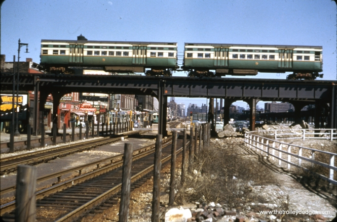 "A Douglas Park train crosses the Van Buren right-of-way near Paulina (1700 W.). We are facing east. This may be circa 1954, as the old ""L"" structure is still in place east of here. It could not be torn down as long as Douglas Park trains needed it to access the Loop. Notice how one of the Garfield tracks makes a dog-leg around the ""L"" supports. Sean Hunnicutt adds, ""this is 6001-6002."""