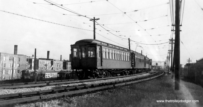 "Wood cars under wire in Evanston in the 1950s. Howard yard is at left. George Trapp: ""Note the variety of car types in the yard: 1000 series NW gate car at far left next to a St. Louis built Articulated with a Pullman unit coupled to it, Baldy 4000 in CTA Green, 6001-6130 series and two rows of Plushie 4000's one in CTA Green the other in CRT Brown. You can also make out 1st and 2nd series of flat door 6000's in station. Photo probably dates to 1952-53."" (Allen T. Zagel Photo, George Trapp Collection)"