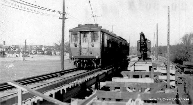 "Here, we have a difference of opinion. George Trapp: ""2 car train on single track is probably circa 1938-1943 as the 4000 series is in Brown/Orange. Believe location is Emerson St. and bridge is being installed where none existed before."" On the other hand, Brian M. Hicks says that this view ""is from Central St. looking North. The 2700 Hampton Pkwy apartments can be seen in the background (1930-31)."" (Allen T. Zagel Photo, George Trapp Collection) Andre Kristopans: ""The shot at Central Street shows construction of the North Shore Channel underway. The embankment is being dug away and the big bridge will soon be going in."""